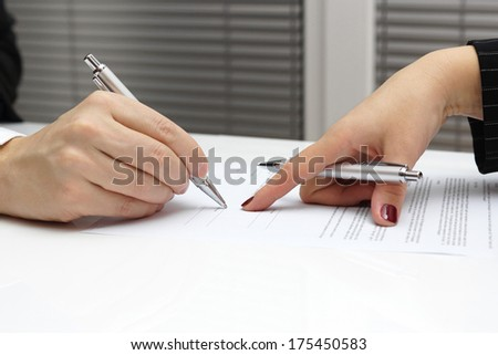 businesswoman point with finger on paper to sign up contract - stock photo