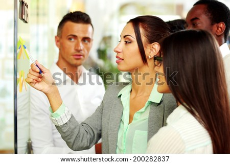 Businesswoman points at the notes in office - stock photo