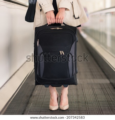 Businesswoman portrait with trolley at Charles de Gaulle airport, Paris.  - stock photo