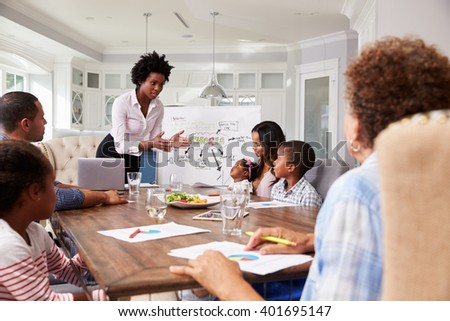 Businesswoman presents meeting to a family in their kitchen - stock photo