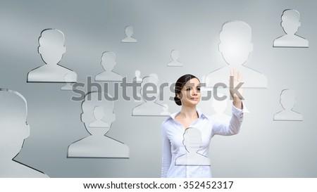 Businesswoman pressing modern social icons on virtual screen - stock photo