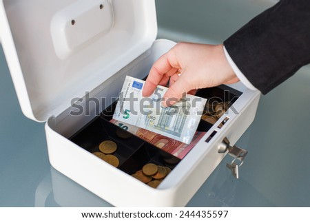 Businesswoman put five euro banknote into safe box - stock photo