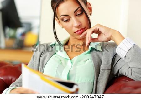 Businesswoman reading magazine in modern office - stock photo