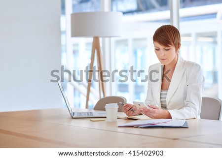 Businesswoman reading message on her phone in modern office - stock photo
