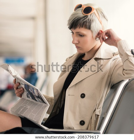 Businesswoman reading newspaper at Charles de Gaulle airport, Paris.  - stock photo