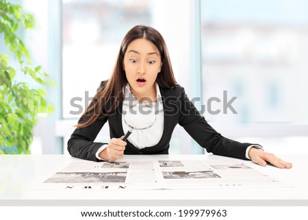 Businesswoman reading the news with scrutiny indoors  - stock photo