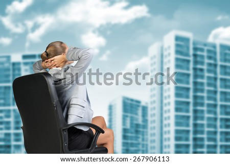 Businesswoman Relaxing on her Chair, with Both Hands Behind her Head, Looking at the Outside Buildings Through Glass Window in the Office - stock photo