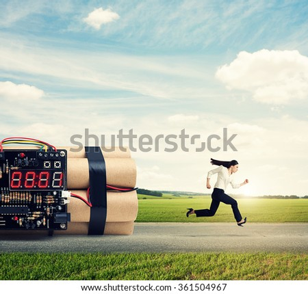businesswoman running away from big bomb on the road - stock photo