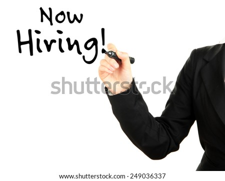 Businesswoman's hand writing Now Hiring at transparent whiteboard - stock photo
