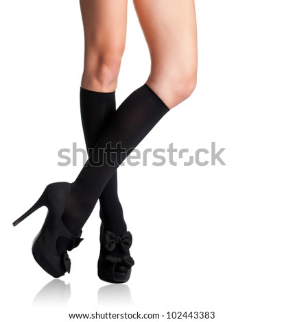 Businesswoman s legs in high stockings and high heels in a white background - stock photo