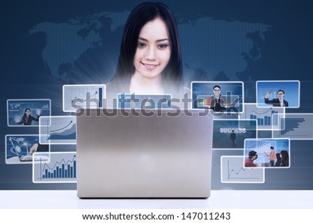 Businesswoman searching online pictures from her laptop on blue background - stock photo