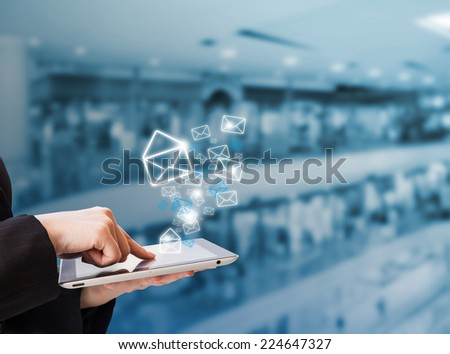 Businesswoman sending email in the shopping mall - stock photo