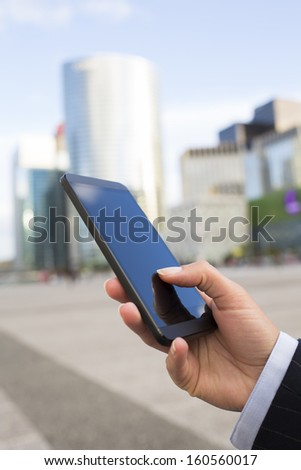 Businesswoman sending messages with her mobile phone in front of building  - stock photo