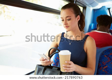 Businesswoman Sending Text Message On Bus - stock photo