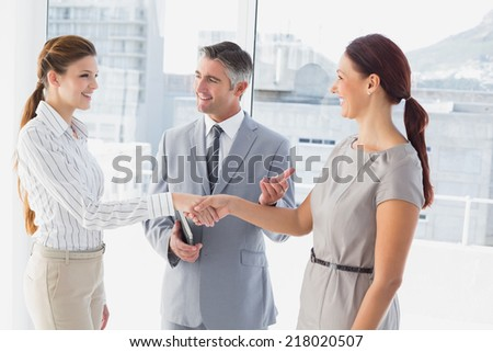 Businesswoman shaking co-workers hand in work - stock photo
