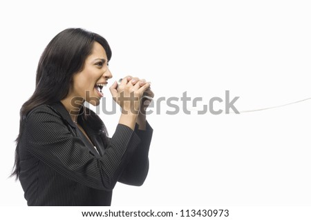 Businesswoman shouting in a tin can phone - stock photo