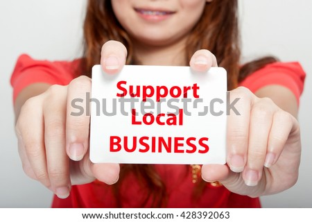 Businesswoman showing card with support local business message, - stock photo