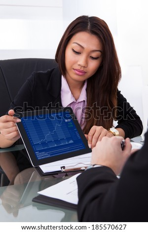 Businesswoman showing digital tablet to male colleague at desk in office - stock photo
