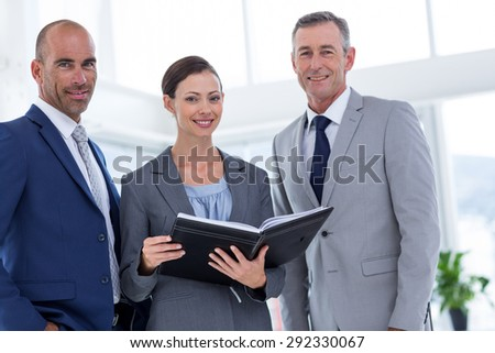 Businesswoman showing her notes to her colleagues and smiling at the camera - stock photo