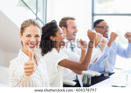 Businesswoman showing her thumbs up in office while team celebrating in background - stock photo