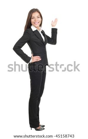Businesswoman showing / pointing at copy space in full length. Confident mixed race chinese / caucasian woman isolated on white background. - stock photo