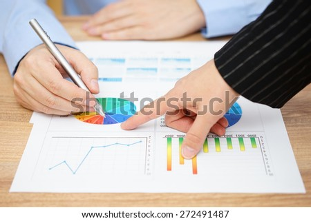 businesswoman showing sales report to his client - stock photo