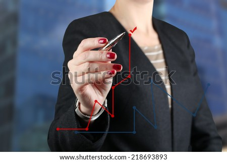 Businesswoman  showing something on  a virtual  graph by  a pen  - stock photo