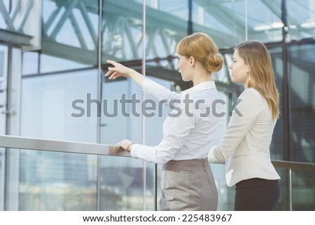 Businesswoman showing something to female colleague from glass wall in office - stock photo