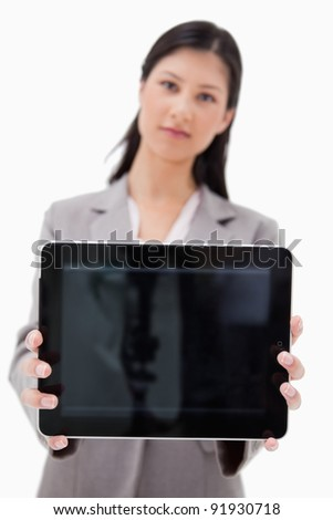 Businesswoman showing tablet screen against a white background - stock photo