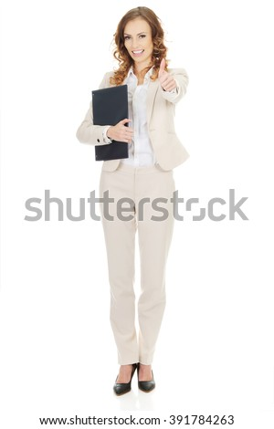 Businesswoman showing thumbs up with clipboard. - stock photo