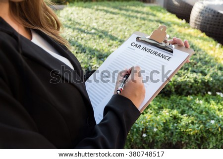 Businesswoman signing a car insurance policy on the street. - stock photo