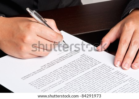 Businesswoman signing a document. - stock photo