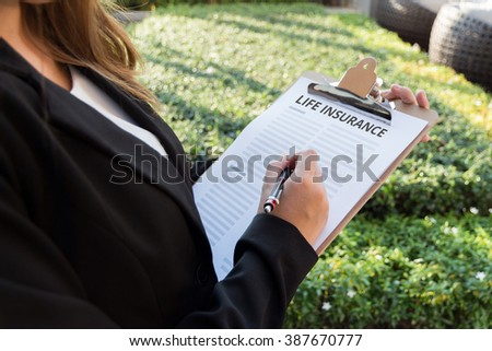 Businesswoman signing a life insurance policy on the street. - stock photo