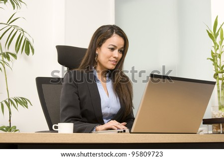 Businesswoman sits at a desk in front of a computer - stock photo