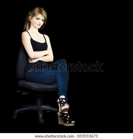 Businesswoman sitting arms folded in confidence on a office chair in a isolated copyspace image on black background - stock photo