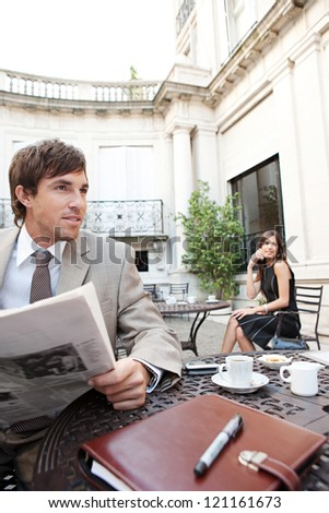 Businesswoman sitting at coffee shop terrace having a cell phone conversation while a businessman sits reading a newspaper in a classic city financial district with office buildings around them. - stock photo