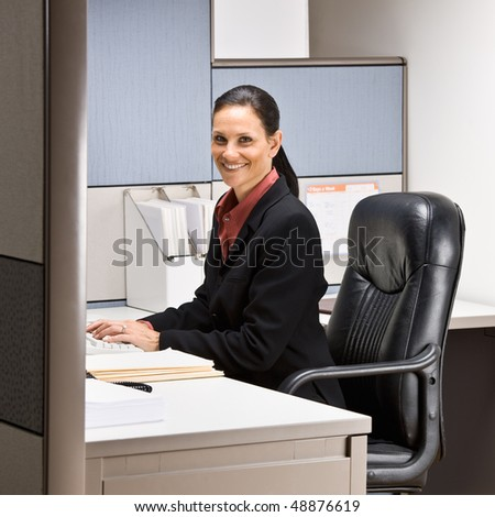 Businesswoman sitting at desk smiling - stock photo