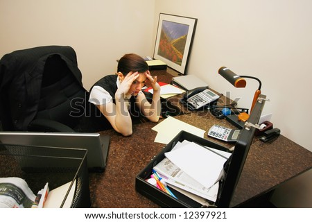 Businesswoman sitting at her desk looking very stressed out with her hands on her temples - stock photo