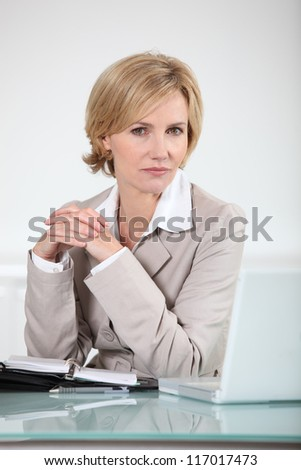 Businesswoman sitting at her laptop with an open diary - stock photo