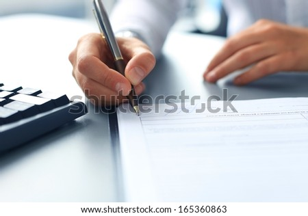 Businesswoman sitting at office desk signing a contract with shallow focus on signature - stock photo