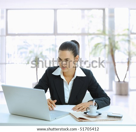 Businesswoman sitting at table in office lobby and using laptop computer. - stock photo