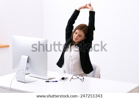 Businesswoman sitting at the table in office and stretching her hands above her head - stock photo
