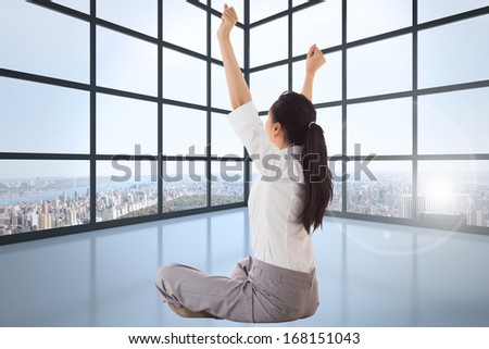 Businesswoman sitting cross legged cheering against room with large windows showing city - stock photo