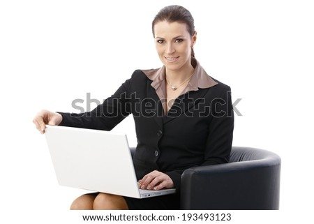 Businesswoman sitting in armchair with laptop computer, smiling at camera, isolated on white. - stock photo