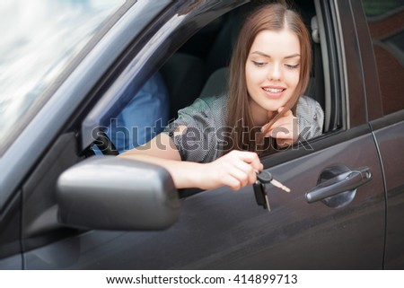 Businesswoman sitting in drivers seat in her car - stock photo