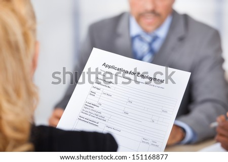 Businesswoman Sitting In Front Of Businessman Holding Application Form - stock photo