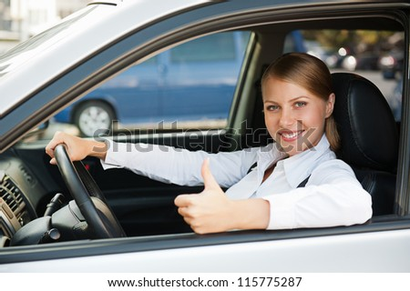 businesswoman sitting in the new car and showing thumbs up - stock photo