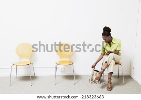 Businesswoman sitting on chair in a waiting room - stock photo