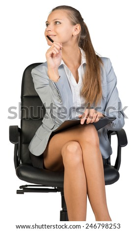 Businesswoman sitting on office chair with pen at her chin and clipboard on her knees, her head half-turned to her right, smiling. Isolated over white background - stock photo