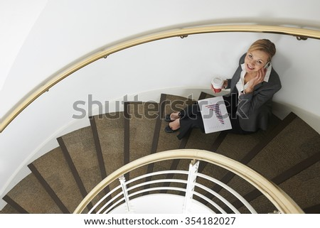 Businesswoman Sitting On Stairs On Mobile Phone - stock photo